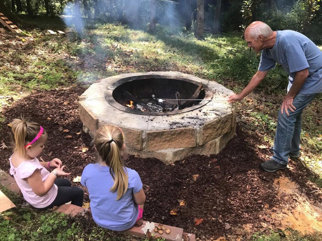 Kids and older man around campfire