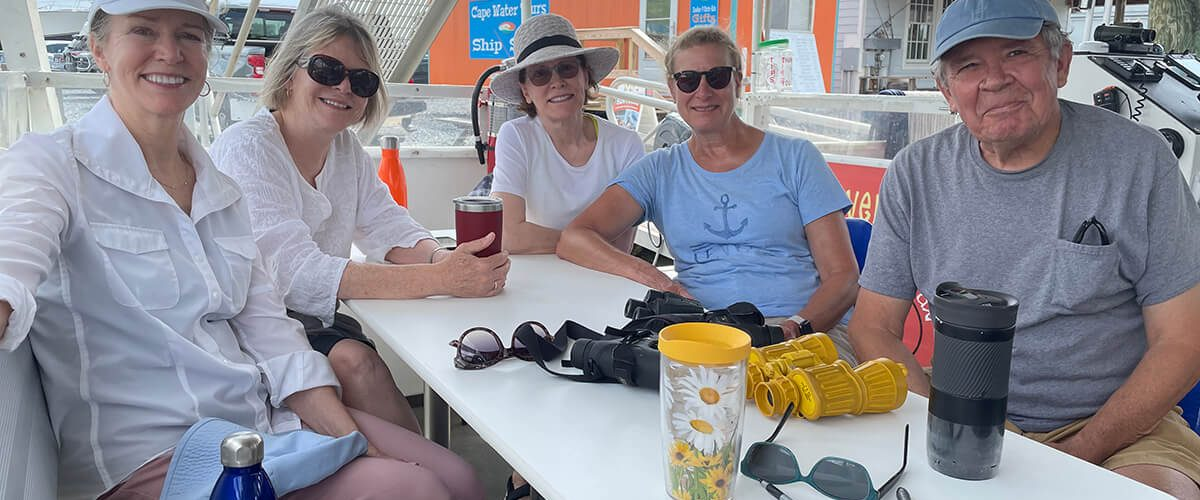 Houseguests (l-r) Bonnie Welsh, Susan Welsh, and Jackie Avignone enjoy the boat ride with their hosts, Lewes residents Andrea Neumann and Bob Fenz.